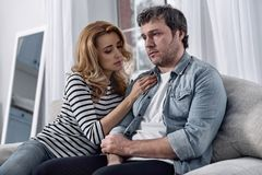 Αγαπώντας σύζυγος σχετικά με τον καταθλιπτικό σύζυγό της καθμένος δίπλα σε τον Στοκ εικόνα με δικαίωμα ελεύθερης χρήσης
