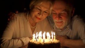 Αγαπώντας την ανώτερη επέτειο εορτασμού ζευγών με το κέικ στο σπίτι το βράδυ φυσώντας κεριά έξω απόθεμα βίντεο
