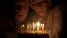 Αγαπώντας την ανώτερη επέτειο εορτασμού ζευγών με το κέικ στο σπίτι το βράδυ φυσώντας κεριά έξω φιλμ μικρού μήκους