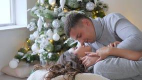 Αγαπώντας τις συγκινήσεις, ο σύζυγος με το θαυμασμό εξετάζει τη σύζυγό του και την φιλά ήπια στο κλίμα των διακοσμημένων Χριστουγ απόθεμα βίντεο