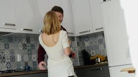 Αγαπώντας τον τύπο που αγκαλιάζει τη χαμογελώντας φίλη του στην κουζίνα τους νωρίς το πρωί με το πρόγευμα απόθεμα βίντεο