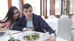 Αγαπώντας το ευτυχές ζεύγος στο εστιατόριο επικοινωνήστε σε Skype σε ένα iPhone με το βίντεο μήκους σε πόδηα αποθεμάτων φίλων φιλμ μικρού μήκους