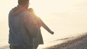 Αγαπώντας το νέο ζεύγος απολαύστε ο ένας τον άλλον το βράδυ με ένα ήρεμο θαλάσσιο νερό απόθεμα βίντεο