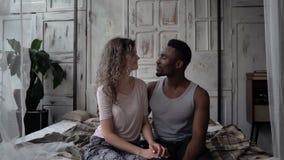 Αγαπώντας το πολυφυλετικό ζεύγος έχει tenderly το πρωί στο διαμέρισμα σοφιτών Ο άνδρας κάνει επάνω την τρίχα, το αγκάλιασμα και τ φιλμ μικρού μήκους