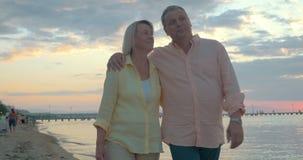 Αγαπώντας το ώριμο ζεύγος που έχει έναν περίπατο στην παραλία φιλμ μικρού μήκους