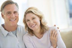 Αγαπώντας το ώριμο ζεύγος που χαμογελά στο σπίτι Στοκ Φωτογραφίες