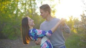 Αγαπώντας τύπος και κορίτσι στο θερινό κήπο στο ηλιοβασίλεμα φιλμ μικρού μήκους
