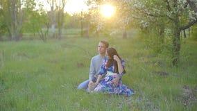Αγαπώντας τύπος και κορίτσι στο θερινό κήπο στο ηλιοβασίλεμα απόθεμα βίντεο