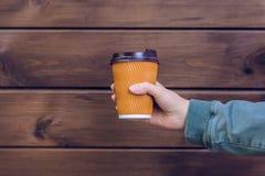 Αγαπώ τον καφέ! Φλιτζάνι του καφέ εκμετάλλευσης χεριών προσώπων ` s μπροστά από το καφετί ξύλινο ποτό τροφίμων υποβάθρου take-$l* στοκ εικόνες