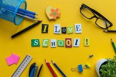 Αγαπώ το σχολείο - κείμενο που γίνεται με τις χαρασμένες επιστολές στο κίτρινο γραφείο με τις προμήθειες γραφείων ή σχολείων στον Στοκ Φωτογραφία