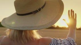 Αγγίξτε το χέρι του ήλιου Μια γυναίκα σε ένα ευρύ καπέλο επεκτείνει το χέρι της στον ήλιο, μια πίσω άποψη απόθεμα βίντεο