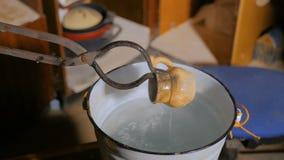 Αγγειοπλάστης που αποσβήνει την καυτή κεραμική κούπα απόθεμα βίντεο