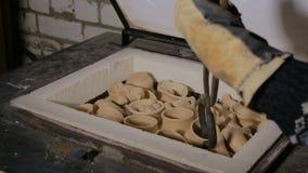 Αγγειοπλάστης που εξετάζει την κεραμική κούπα απόθεμα βίντεο