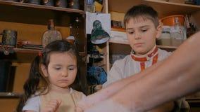 Αγγειοπλάστης που επιδεικνύει πώς να εργαστεί με κεραμικό στο στούντιο αγγειοπλαστικής απόθεμα βίντεο