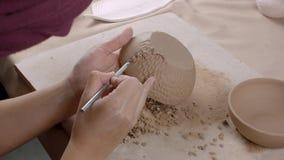 Αγγειοπλάστης που κάνει τη διακόσμηση στο κεραμικό πιάτο Ο αγγειοπλάστης γυναικών βάζει τη σύσταση στο πιάτο E απόθεμα βίντεο