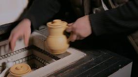 Αγγειοπλάστης που τοποθετεί τα κεραμικά εμπορεύματα στον κλίβανο αγγειοπλαστικής απόθεμα βίντεο