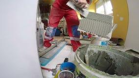 Αγγειοπλάστης που χρησιμοποιεί χαραγμένο κατασκευή Trowel με το κονίαμα για την εργασία κεραμιδιών φιλμ μικρού μήκους