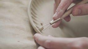 Αγγειοπλάστης χεριών: στρέθιμο της προσοχής ενός σχεδίου σε ένα πιάτο αργίλου Ο αγγειοπλάστης κάνει το πιάτο φιλμ μικρού μήκους