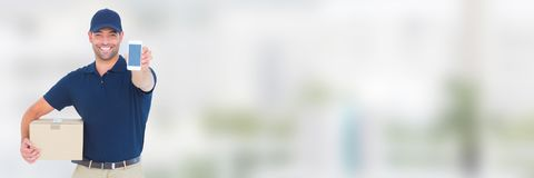 Αγγελιαφόρος παράδοσης με το δέμα και τηλέφωνο μπροστά από το θολωμένο υπόβαθρο Στοκ φωτογραφία με δικαίωμα ελεύθερης χρήσης