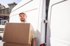 Αγγελιοφόρος που παραδίδει το δέμα, που στέκεται δίπλα στο φορτηγό του Στοκ Εικόνα