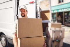 Αγγελιοφόρος που παραδίδει το δέμα, που στέκεται δίπλα στο φορτηγό του Στοκ Φωτογραφίες
