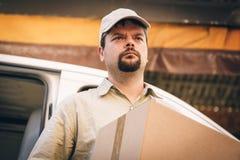 Αγγελιοφόρος που παραδίδει το δέμα, που στέκεται δίπλα στο φορτηγό του Στοκ φωτογραφία με δικαίωμα ελεύθερης χρήσης