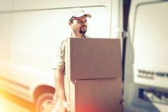 Αγγελιοφόρος που παραδίδει το δέμα, που στέκεται δίπλα στο φορτηγό του Στοκ Φωτογραφία