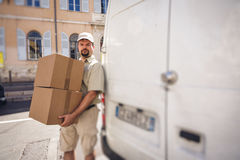 Αγγελιοφόρος που παραδίδει το δέμα, που στέκεται δίπλα στο φορτηγό του Στοκ φωτογραφίες με δικαίωμα ελεύθερης χρήσης