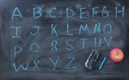 Αγγλικές επιστολές αλφάβητου που γράφονται στον πίνακα κιμωλίας με τη γόμα και στοκ εικόνα