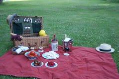 Αγγλικό καλάθι πικ-νίκ στο κάλυμμα πικ-νίκ με πολλά λιχουδιές και ποτά Στοκ Εικόνα