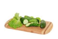 Αγγούρια και πράσινη σαλάτα που βρίσκονται στον τέμνοντα πίνακα Στοκ Εικόνες