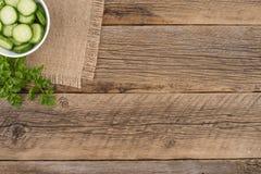 Αγγούρια περικοπών σε ένα άσπρο κύπελλο στον παλαιό ξύλινο πίνακα Στοκ Φωτογραφία