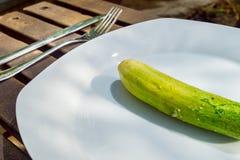 Αγγούρι στο άσπρο πιάτο στο ξύλινο υπόβαθρο Στοκ Φωτογραφίες