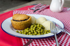 Αγγλική παραδοσιακή πίτα με τις πολτοποιηίδες πατάτες και πράσινα μπιζέλια κήπων με το ζωμό στον κόκκινο πίνακα Στοκ Φωτογραφία