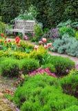 Αγγλικός κήπος με μια πορεία περιπάτων που οδηγεί στον κενό πάγκο Στοκ εικόνα με δικαίωμα ελεύθερης χρήσης