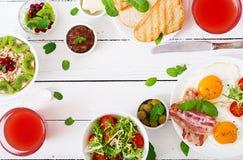 Αγγλικό πρόγευμα - τηγανισμένα αυγό, ντομάτες και μπέϊκον πρόγευμα δύο oatmeal Στοκ Εικόνες