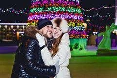 Αγκάλιασμα και γέλια ζεύγους στο τετράγωνο Χριστουγέννων τη νύχτα στοκ εικόνες