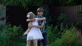 Αγκάλιασμα μικρών κοριτσιών και αγοριών που φαίνεται μεταξύ τους συγκινήσεις και φιλία των παιδιών απόθεμα βίντεο