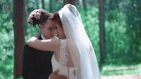 Αγκάλιασμα Newlyweds, που στέκεται στα ξύλα, κινηματογράφηση σε πρώτο πλάνο φιλμ μικρού μήκους