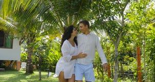 Αγκάλιασμα περπατήματος ζεύγους στον τροπικό κήπο κοντά στο σπίτι βιλών, τον ευτυχείς άνδρα και τη γυναίκα που φιλούν υπαίθρια το απόθεμα βίντεο