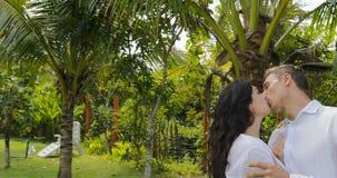 Αγκάλιασμα περπατήματος ζεύγους στον τροπικό κήπο κοντά στο σπίτι βιλών, τον ευτυχείς άνδρα και τη γυναίκα που φιλούν υπαίθρια το φιλμ μικρού μήκους