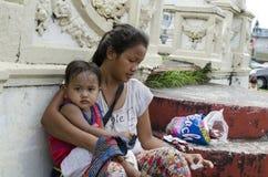 Αγκαλιάζοντας γιος μωρών μητέρων στα πωλώντας κεριά patio ναυπηγείων εκκλησιών Στοκ Φωτογραφία