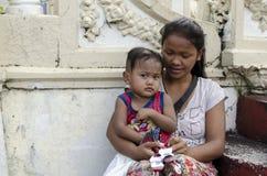 Αγκαλιάζοντας γιος μωρών μητέρων στα πωλώντας κεριά patio ναυπηγείων εκκλησιών Στοκ φωτογραφίες με δικαίωμα ελεύθερης χρήσης