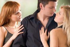 αγκαλιάζοντας τον άνδρα υπαίθρια δύο νεολαίες γυναικών στοκ εικόνα