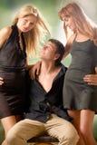 αγκαλιάζοντας τον άνδρα υπαίθρια δύο νεολαίες γυναικών στοκ φωτογραφίες