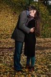 Αγκαλιάσματα ζεύγους σε ένα πάρκο πτώσης Χρυσό φθινόπωρο στο υπόβαθρο με τα φύλλα και τα δέντρα, φύλλωμα Στοκ φωτογραφία με δικαίωμα ελεύθερης χρήσης