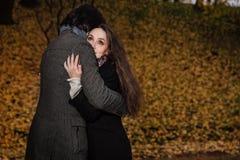 Αγκαλιάσματα ζεύγους σε ένα πάρκο πτώσης Χρυσό φθινόπωρο στο υπόβαθρο με τα φύλλα και τα δέντρα, φύλλωμα Στοκ Φωτογραφίες