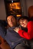 Αγκαλιά ζεύγους στον καναπέ από την άνετη πυρκαγιά κούτσουρων Στοκ φωτογραφίες με δικαίωμα ελεύθερης χρήσης