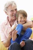 Αγκαλιάζοντας εγγονός παππούδων στο κάθισμα κήπων Στοκ Φωτογραφίες