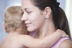 Αγκαλιάζοντας κοριτσάκι μητέρων στοκ φωτογραφίες